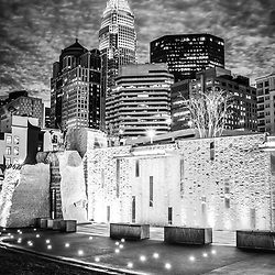 Charlotte cityscape at night black and white photo with Romare Bearden Park waterfall wall and downtown Charlotte buildings against a stormy sky. Charlotte, North Carolina is a major city in the Eastern USA.