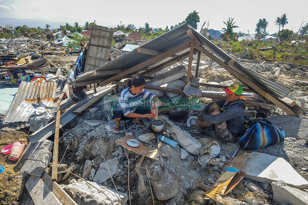 October 3, 2018 - Palu, Central Sulawesi, Indonesia - Agustin (51) cooks for her husband Baktiar (51) between the ruins of his house in Balaroa village after the earthquake in Palu. A deadly earthquake measuring 7.7 magnitude and the tsunami wave caused by it has destroyed the city of Palu and much of the area in Central Sulawesi. According to the officials, death toll from devastating quake and tsunami rises to 1,347, around 800 people in hospitals are seriously injured and some 62,000 people have been displaced in 24 camps around the region. (Credit Image: © Hariandi Hafid/SOPA Images via ZUMA Wire)