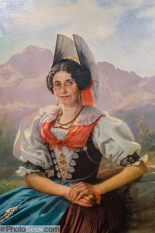 Attractive 1861 painting of a woman in traditional Appenzell costume, a variation of the Swiss National folk dress. Appenzell Museum, which is in the town hall, shows a cross section of the Swiss Canton's history and culture. Appenzell village is in Appenzell Innerrhoden, Switzerland's most traditional and smallest-population canton (second smallest by area).