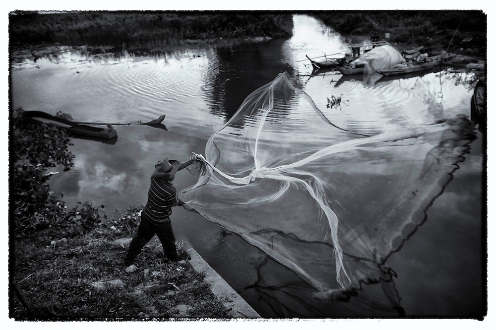 A Cambodian man cast his fishing net in a small lake on the outskirts of Phnom Penh.