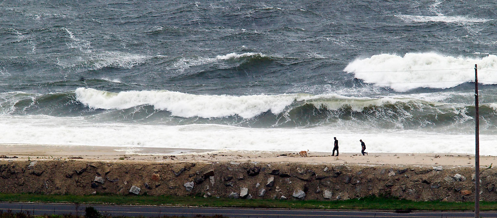 (PPAGE1) SEA BRIGHT 9/18/2003  Large waves pound the beach of Sandy Hook as a people walk along the shore during the storm.  This was taken from Twin Lights in Highlands.  The road is Ocean Ave just south of Highlands bridge.  Michael J. Treola Staff Photographer.......MJT