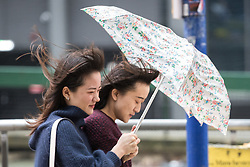 © Licensed to London News Pictures . 20/02/2017 . Manchester , UK . Two women share an umbrella in squally showers in Manchester City Centre , this afternoon (20th February 2017) . Photo credit: Joel Goodman/LNP