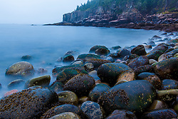 Cobblestones and Otter Cliffs on a foggy morning in Maine's Acadia National Park.