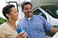 Mid-adult couple standing beside caravan