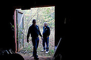 "Ghost hunters Andy Carter and his uncle Grady stand in the doorway of a cotton gin that dates back to the 1830s and is rumored to be haunted to follow-up on an investigation. The team brings flashlights, audio recorders, video recorders and night vision cameras to gather evidence of ghosts. The ""paranormal investigators"" of Twisted Dixie are Grady Carter, Andy Carter, Chris Carter (all related), and Chris Phillips, seen in Antreville, South Carolina November 4, 2011."