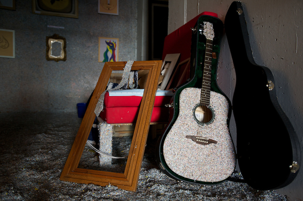 March 27, 2012 - Dublin, Ireland: A guitar covered with shredded money stands among other objects in the main hall of the Billion Euro House art installation by the Irish artist Frank Buckley. ..Worthless euros, taken out of circulation and shredded by Irelands Central Bank, formes the interior walls of an apartment that Mr. Buckley does not own in a building left vacant by the countrys economic ruin...The artist decided to call the apartment  built from thousands of bricks of shredded, decommissioned cash (each brick contains, roughly, what used to be 50,000 euros)  the Billion Euro House. He reckons that about 1.4 billion euros actually went into it, but the joke, of course, is that it is worth simultaneously so much and so little...A large gravestone beside the main door, announces that Irish sovereignty died in 2010, the year that the government accepted an international bailout so larded with onerous conditions that the Irish will be paying for it for years to come. (Paulo Nunes dos Santos/Polaris)