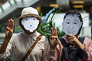 "01 JUNE 2014 - BANGKOK, THAILAND:  Women wearing masks hold up a three fingered salute during a protest against the Thai military coup at Terminal 21 a popular shopping mall in Bangkok. The salute is from the movie ""The Hunger Games"" and symbolizes it admiration, thanks and good-bye to a loved one. In this case, the loved one is reportedly Thai democracy. The Thai army seized power in a coup that unseated a democratically elected government on May 22. Since then there have been sporadic protests against the coup. The protests Sunday were the largest in several days and seemed to be spontaneous ""flash mobs"" that appeared at shopping centers in Bangkok and then broke up when soldiers arrived. Protest against the coup is illegal and the junta has threatened to arrest anyone who protests the coup. There was a massive security operation in Bangkok Sunday that shut down several shopping areas to prevent the protests but protestors went to malls that had no military presence.   PHOTO BY JACK KURTZ"