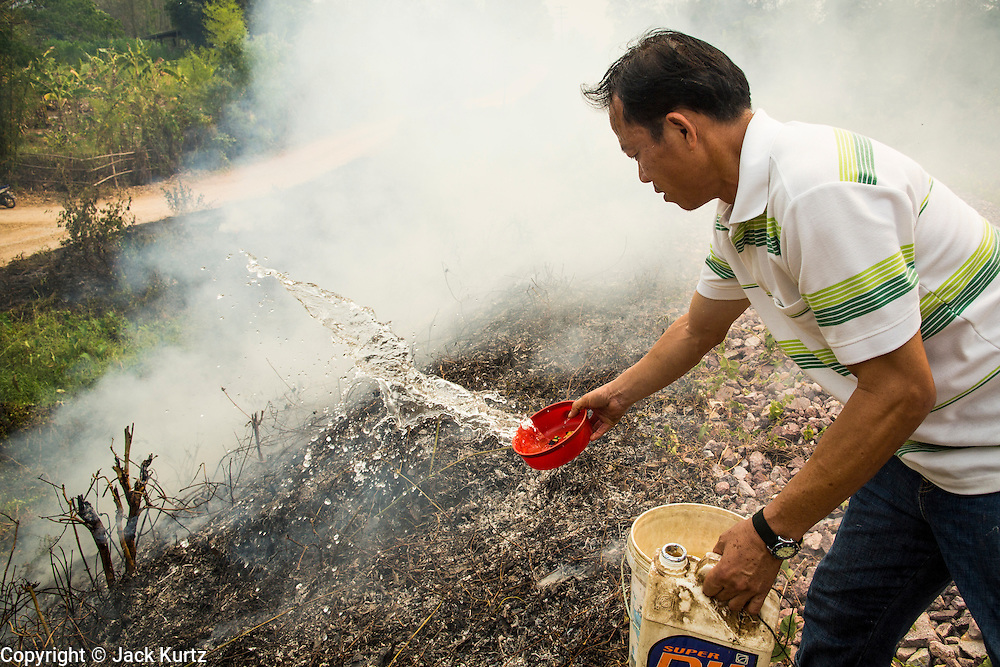 "09 APRIL 2013 - KHUNTAN, LAMPHUN, THAILAND:  An assistant village headman from Khuntan, Lamphun province, throws water on a grassfire burning on a roadside in the community. The ""burning season,"" which roughly goes from late February to late April, is when farmers in northern Thailand burn the dead grass and last year's stubble out of their fields. The burning creates clouds of smoke that causes breathing problems, reduces visibility and contributes to global warming. The Thai government has banned the burning and is making an effort to control it, but the farmers think it replenishes their soil (they use the ash as fertilizer) and it's cheaper than ploughing the weeds under.     PHOTO BY JACK KURTZ"