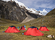 In Alpamayo Valley at 13,860 feet / 4200 meters, we camp with red tents under Nevado Alpamayo (19,511 ft / 5947 m) in the Cordillera Blanca, Andes Mountains, Peru, South America. Afternoon of day 7 of 10 days trekking around Alpamayo, in Huascaran National Park (UNESCO World Heritage Site).