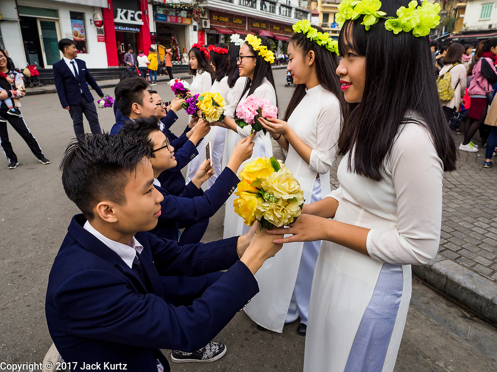 """24 DECEMBER 2017 - HANOI, VIETNAM: Students pretend to stage a group proposal in the old quarter of Hanoi. The old quarter is the heart of Hanoi, with narrow streets and lots of small shops but it's being """"gentrified"""" because of tourism and some of the shops are being turned into hotels and cafes for tourists and wealthy Vietnamese.           PHOTO BY JACK KURTZ"""