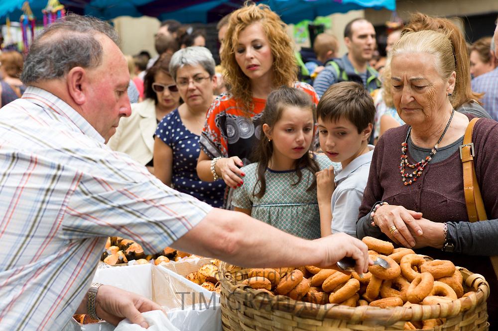 Locals buying churro doughnut snacks in the street during San Fermin Fiesta at Pamplona, Navarre, Northern Spain