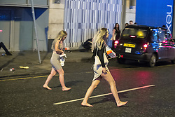 "© Licensed to London News Pictures . 17/12/2016 . Manchester , UK . Two women cross Withy Grove . Revellers out in Manchester City Centre overnight during "" Mad Friday "" , named for being one of the busiest nights of the year for the emergency services in the UK . Photo credit : Joel Goodman/LNP"
