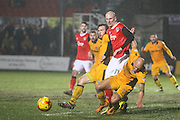 David Pipe of Newport County clears the ball, under pressure from Kevin Ellison of Morecambe FC during the EFL Sky Bet League 2 match between Newport County and Morecambe at Rodney Parade, Newport, Wales on 21 February 2017. Photo by Andrew Lewis.