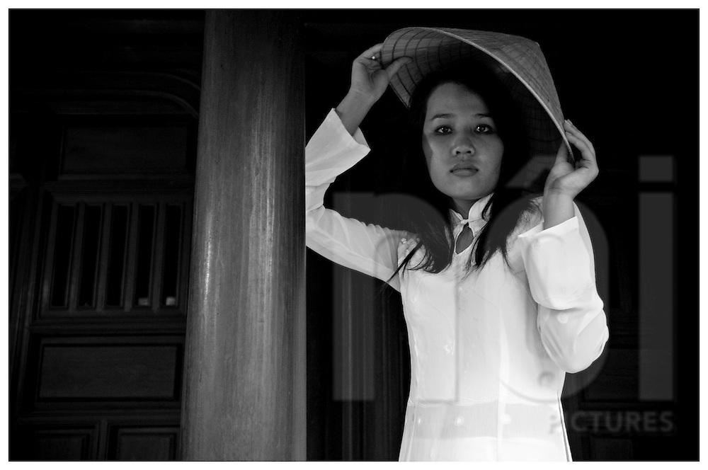 Beauty portrait of a vietnamese woman removing a conical hat. Khanh Hoa area, Vietnam, Asia