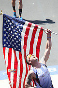 April 21, 2014 - Boston, Massachusetts, U.S. - <br /> <br /> Boston Marathon 2014<br /> <br /> Tens of thousands of runners cross the finish line of the 2014 Boston Marathon in Boston, Massachusetts. A man lifts the American flag as he crosses the finish line.<br /> ©Exclusivepix