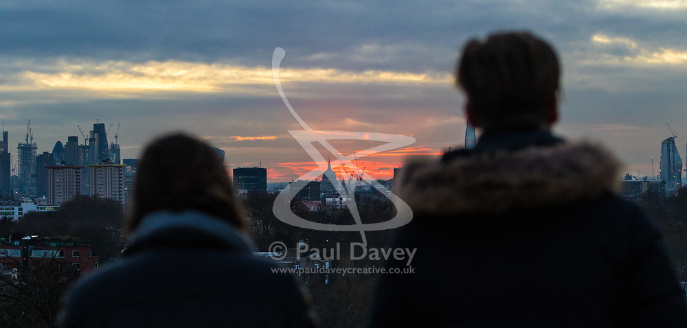 London, November 30 2017. A couple enjoy the spectacle as the sun rises over the London skyline, seen from Primrose Hill, on a chilly London morning when overnight temperatures plunged to below freezing. © Paul Davey