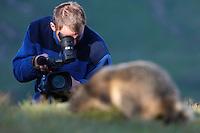 Photographer with marmot (model release 02/08/HTNP), Hohe Tauern National Park, Carinthia, Austria