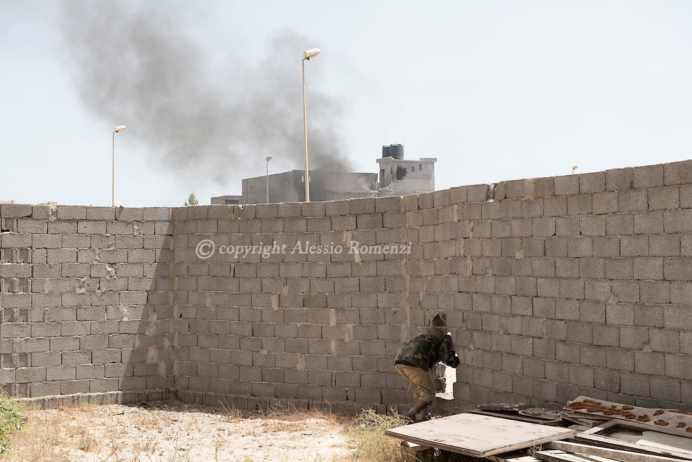 Libya: in 700 neighbourhood in Sirte a fighter affiliated with Libya's Government of National Accord's (GNA) passes through a hole in the wall during clashes with ISIS. Alessio Romenzi
