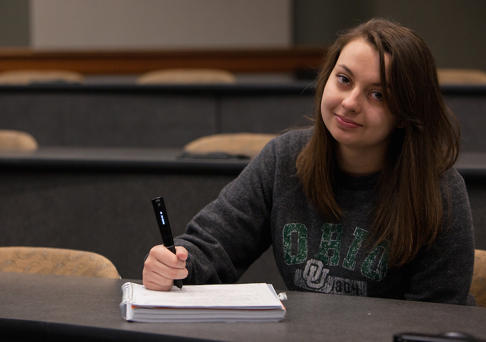 Ohio University student Paige Ludwin poses for a portrait with the special pen that she uses to take notes in class. The pen includes an audio recording device. Photo by Lauren Pond