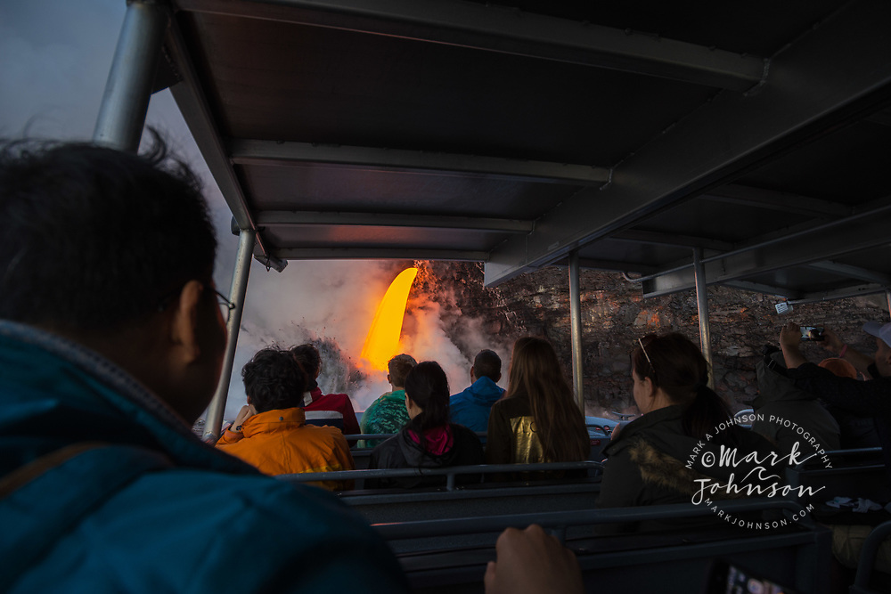 Tourists in a tour boat viewing the spectacular lava flow into the ocean at Kamokuna, Big Island, Hawaii