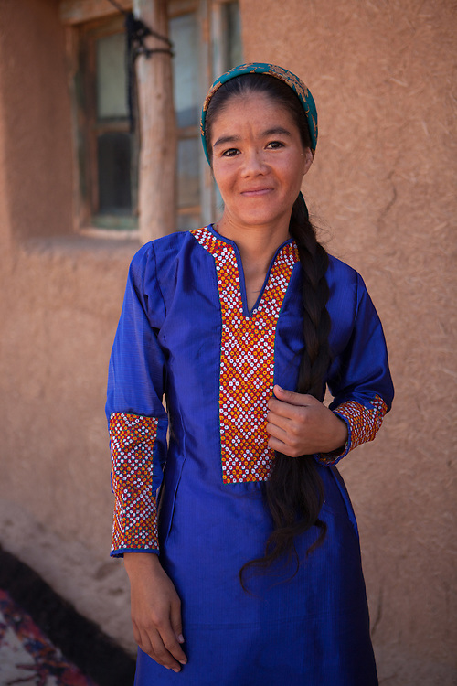 A young woman, also a poet, stands outside the family home in the desert village of Damla, Turkmenistan