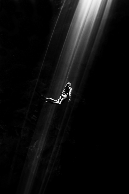 México, Quintana Roo, Tulum. A free diver champion ascending through the sunrays at cenote The Pit.