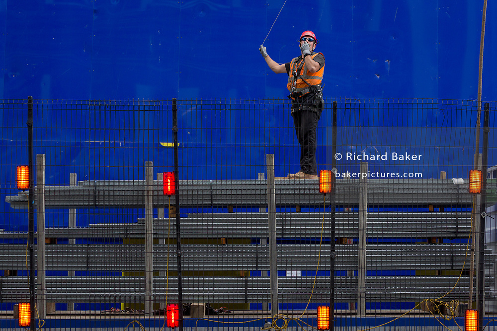 A construction worker supervises the lifting by crane of new flooring to an upper floor at the new development high-rise development at 22 Bishopsgate in the City of London - the capital's financial district, on 21st August 2018, in London, England. 22 Bishopsgate is a commercial skyscraper under construction in London, United Kingdom. It will occupy a prominent site on Bishopsgate, in the City of London financial district, and is set to stand 278 m tall with 62 storeys. The project replaces an earlier plan for a 288 m tower named The Pinnacle, on which construction was started in 2008 but suspended in 2012 following the Great Recession,