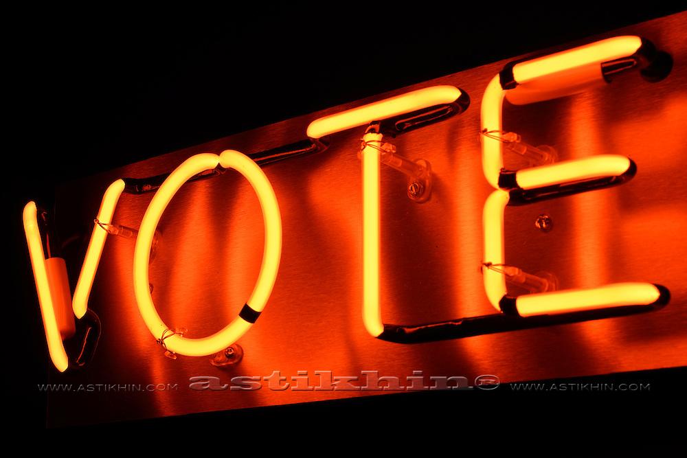 A neon VOTE sign glowing orange.