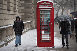 © licensed to London News Pictures. London, UK 18/01/2013. People walking past a telephone booth cover with snow as snow hits London on Friday 18, January 2013. Photo credit: Tolga Akmen/LNP
