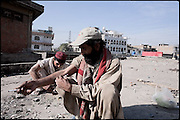 "Addicts inject doses of heroin hid from the eyes of the local people on a roof top of a building. Morgh Mandi,  Rawalpindi, Pakistan, on friday, November 28 2008.....""Pakistan is one of the countries hardest hits by the narcotics abuse into the world, during the last years it is facing a dramatic crisis as it regards the heroin consumption. The Unodc (United Nations Office on Drugs and Crime) has reported a conspicuous decline in heroin production in Southeast Asia, while damage to a big expansion in Southwest Asia. Pakistan falls under the Golden Crescent, which is one of the two major illicit opium producing centres in Asia, situated in the mountain area at the borderline between Iran, Afghanistan and Pakistan itself. .During the last 20 years drug trafficking is flourishing in the Country. It is the key transit point for Afghan drugs, including heroin, opium, morphine, and hashish, bound for Western countries, the Arab states of the Persian Gulf and Africa..Hashish and heroin seem to be the preferred drugs prevalence among males in the age bracket of 15-45 years, women comprise only 3%. More then 5% of whole country's population (constituted by around 170 milion individuals),  are regular heroin users, this abuse is conspicuous as more of an urban phenomenon. The substance is usually smoked or the smoke is inhaled, while small number of injection cases have begun to emerge in some few areas..Statistics say, drug addicts have six years of education. Heroin has been identified as the drug predominantly responsible for creating unrest in the society."""