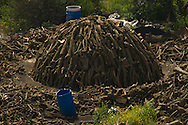 Mevo Dotan Charcoal has been made by various methods. The traditional method in Britain used a clamp. This is essentially a pile of wooden logs (e.g. seasoned oak) leaning against a chimney (logs are placed in a circle). The chimney consists of 4 wooden stakes held up by some rope. The logs are completely covered with soil and straw allowing no air to enter. It must be lit by introducing some burning fuel into the chimney; the logs burn very slowly (cold fire) and transform into charcoal in a period of 5 days' burning. If the soil covering gets torn (cracked) by the fire, additional soil is placed on the cracks. Once the burn is complete, the chimney is plugged to prevent air from entering.