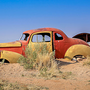 Old and rusty car wreck at the last gaz station before the Namib desert. Solitaire, Namibia.