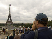 tourist filming family and Eiffel tower