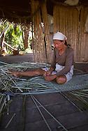 Woman weaving mat, Peru