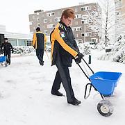 Nederland, Rotterdam, 17 december 2010. Weeralarm, zware sneeuwval in de Randstad. Medewerkers van Stadstoezicht, gekleed in dikke winterkleding / nieuwe uniform uniformen, maken het trottoir naar de ingang van het ouderenhuis vrij van sneeuw. Wegscheppen van sneeuw, pad maken in de sneeuw. Gemeentelijke diensten, dienstbaar zijn aan de burger, een handje helpen, dieners, ambtenaren. Foto: David Rozing