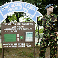"PANMUNJOM, MAY-16: Flight lieutenant David Jobster from Scotland stands next to a billboard in front of  the ""world's most dangerous"" golf course in the DMZ, Korea."