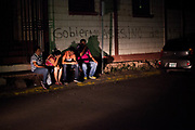 """The family of a 15-year-old girl have just learned that she had been raped, tortured and killed. Her body was found tied up in the woods, it is thought she was killed by a gang. Behind the family the wall is painted with the words """"Gobierno asesino de JOH"""" or (President) Juan Orlando Hernandez' Killer Government. Many blame the current government for the violence in the country, and question the legitimacy of government since the coup against Mel Zelaya. 3rd August 2017."""