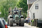 Nederland, Empel, 20-5-2015 Een grote tractor, trekker, rijdt op een smalle dijk. Andere weggebruikers moeten hier goed rekening mee houden en het kan gevaarlijke situaties, verkeerssituaties opleveren. Ook huizen die vlak langs de weg liggen kunnen schade van zwaar verkeer oplopen.Foto: Flip Franssen/Hollandse Hoogte