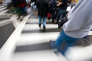 Blurred legs and feet of pedestrians crossing 5th avenue in New York city.