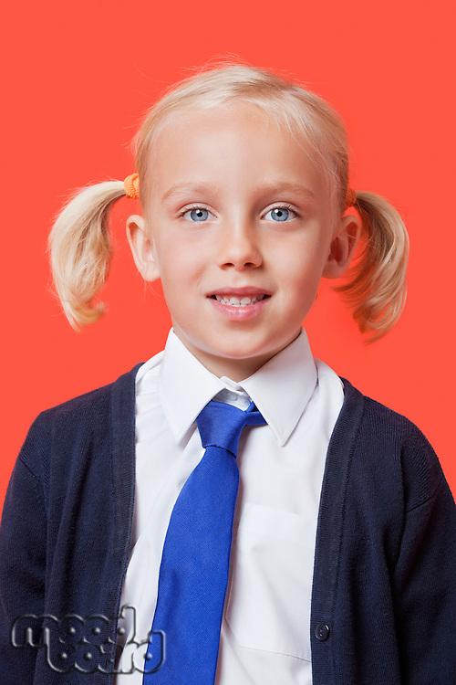 Portrait of a happy schoolgirl in uniform over orange background