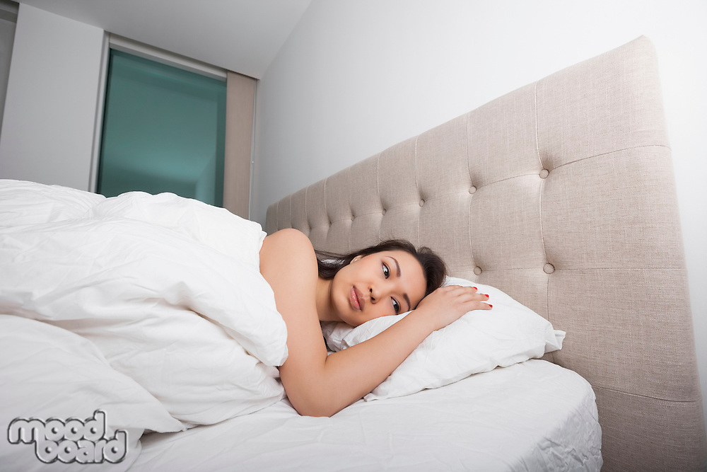 Thoughtful young woman lying in bed
