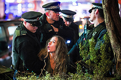 © Licensed to London News Pictures . 01/01/2016 . Manchester , UK . Police detain a woman . Revellers in Manchester on a New Year night out at the clubs around the city centre's Printworks venue . Photo credit : Joel Goodman/LNP
