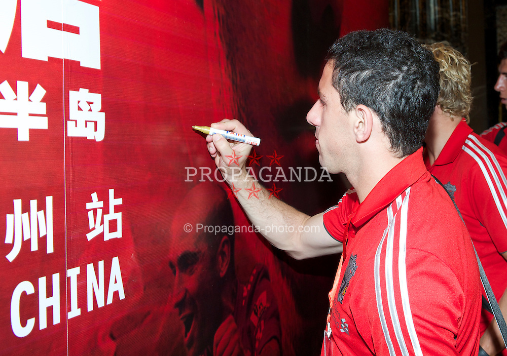 GUANGZHOU, CHINA - Monday, July 11, 2011: Liverpool's Maximiliano Ruben Maxi Rodriguez signs his name on a branding board as the team arrive at the Chateau Star River Hai Yi Peninsula during the club's Asia Tour. (Photo by David Rawcliffe/Propaganda)