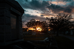 "Der Metairie Cemetery ist ein ländlicher Friedhof in New Orleans, Louisiana, USA. Der Name laesst faelschlicherweise vermuten, dass sich der Friedhof in Metairie, Louisiana, befindet. Er befindet sich jedoch innerhalb der Stadtgrenzen von New Orleans an der Metairie Road. Diese Grabstaette war zuvor eine Pferderennbahn, des 1838 gegründeten Metairie Race Course. Auf der Rennstrecke fand am 1. April 1854 das berühmte Lexington-Lecomte-Rennen statt, das als ""Norden gegen den Süden"" -Rennen bezeichnet wurde. Der frühere Praesident Millard Fillmore war anwesend. Wegen des amerikanischen Bürgerkriegs wurde das Rennen eingestellt und als konfoederiertes Lager (Camp Moore) genutzt, bis David Farragut im April 1862 New Orleans für die Union einnahm. Der Metairie Cemetery wurde danach auf dem Gelände des alten Metairie Race Course errichtet. Im Bild ein Sonnenuntergang und Graeber, aufgenommen am 15.02.2020, New Orleans, Vereinigte Staaten von Amerika // Metairie Cemetery is a rural cemetery in New Orleans, Louisiana, United States. The name has caused some people to mistakenly presume that the cemetery is located in Metairie, Louisiana; but it is located within the New Orleans city limits, on Metairie Road (and formerly on the banks of the since filled-in Bayou Metairie). This site was previously a horse racing track, Metairie Race Course, founded in 1838. The race track was the site of the famous Lexington-Lecomte Race, April 1, 1854, billed as the ""North against the South"" race. Former President Millard Fillmore attended. While racing was suspended because of the American Civil War, it was used as a Confederate Camp (Camp Moore) until David Farragut took New Orleans for the Union in April 1862. Metairie Cemetery was built upon the grounds of the old Metairie Race Course after it went bankrupt. The race track, which was owned by the Metairie Jockey Club, refused membership to Charles T. Howard, a local resident who had gained his wealth by starting the first Louisi"