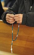 A woman prays the rosary in church. (Sam Lucero photo)