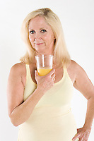 Portrait of a beautiful mature woman enjoying a glass of orange juice