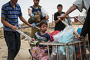 Civilians flee the recently liberated 17 Tammuz neighbourhood in west Mosul while a journalist hands out bottles of water on May 19, 2017.