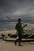 Antandroy fisherman walking past pirogues on beach. The narrow wooden canoes with their one stabalizer are remarkably sea worthy. The sail is made from cotton or woven plasitc sacking. Lavanono fishing village, south coast of MADAGASCAR