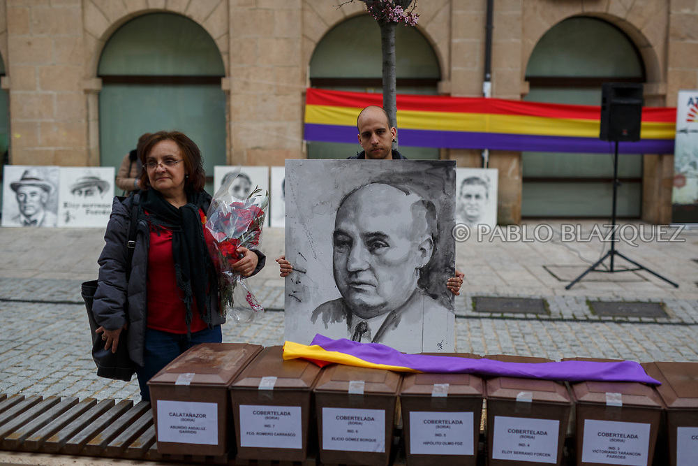 14/04/2018. A portrait depicting Spain's Civil war victim Abundio Andaluz is hold by his great grandson (R) next to her granddaughter Ana Maria Andaluz Caballero (L) and coffins containing the bodies of victims of Spain Civil War exhumed in Cobertelada and Calata&ntilde;azor in the center of Soria during a homage to hand the remains to their relatives on April 14, 2018 in Soria, Spain. La Asociacion Soriana Recuerdo y Dignidad (ASRD) 'The Soria Association for Memory and Dignity' celebrated a tribute to hand over the remains of civil war victims to their families. The Society of Sciences of ARANZADI helped with the research, exhumation and identification of the bodies, after villagers passed the information about the mass grave, 81 years after the assassination took place, to the ASRD. Seven people were assassinated around August 25, 1936 by Falangists, as part of General Francisco Franco armed forces, and buried in the 'Fosa de los Maestros' (Teachers Mass Grave) near Cobertelada, Soria, after being taken from prison of Almazan during the Spanish Civil War. Five of them were teachers in the region, and also friends of Spanish writer Antonio Machado. The other two still remain unidentified. Another body was assassinated by Falangists accompanied by a priest in 1936, and was exhumed on 23 September of 2017 near Calata&ntilde;azor, Soria. It belonged to Abundio Andaluz, a politician, lawyer and musician in Soria.<br /> Spain's Civil War took the lives of thousands of people on both sides, and civilians. But Franco continued his executions after the war has finished. Teachers, as part of the education sector, were often a target of Franco's forces. Spanish governments has never done anything to help the victims of the Civil War and Franco's dictatorship while there are still thousands of people missing in mass graves around the country. (&copy; Pablo Blazquez)