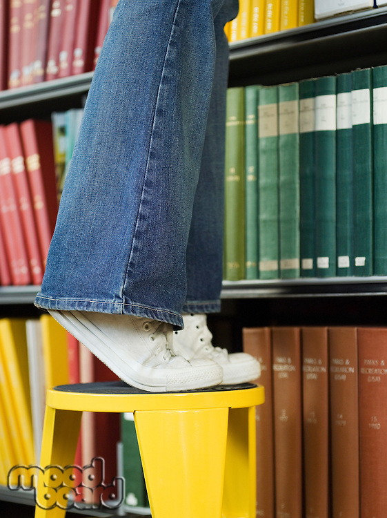 Young woman standing on stool reaching for book low section